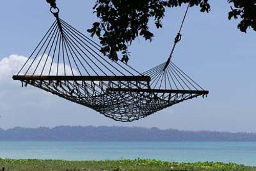 Foto van een hangmat boven een tropische zee